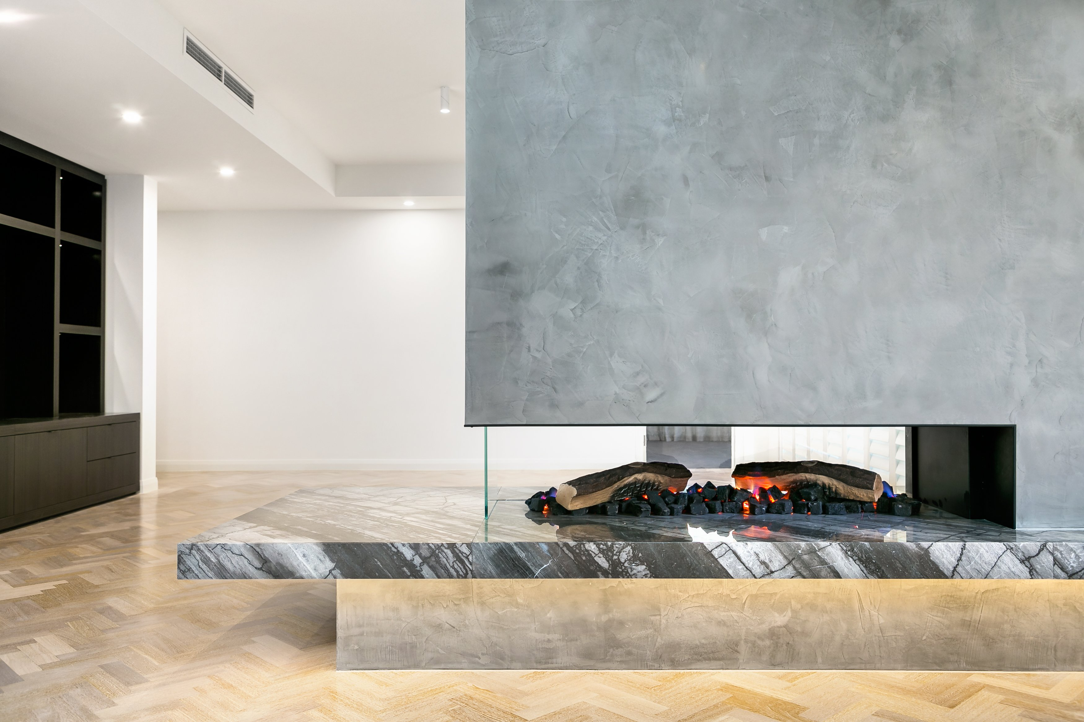 3-sided modern fireplace in apartment renovation by Canny