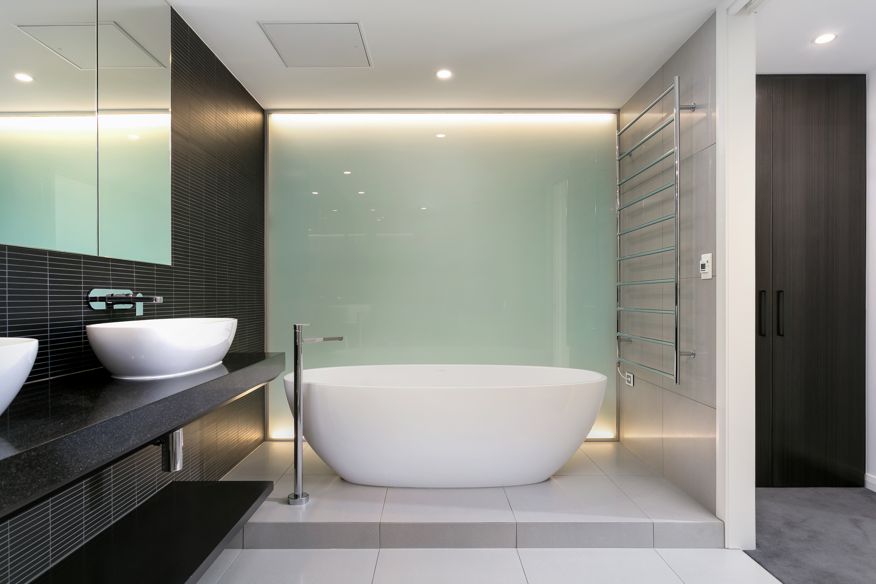 The bathtub stands in a private cove centered on a backlit smoked glass wall, making an ethereal glow in the space.