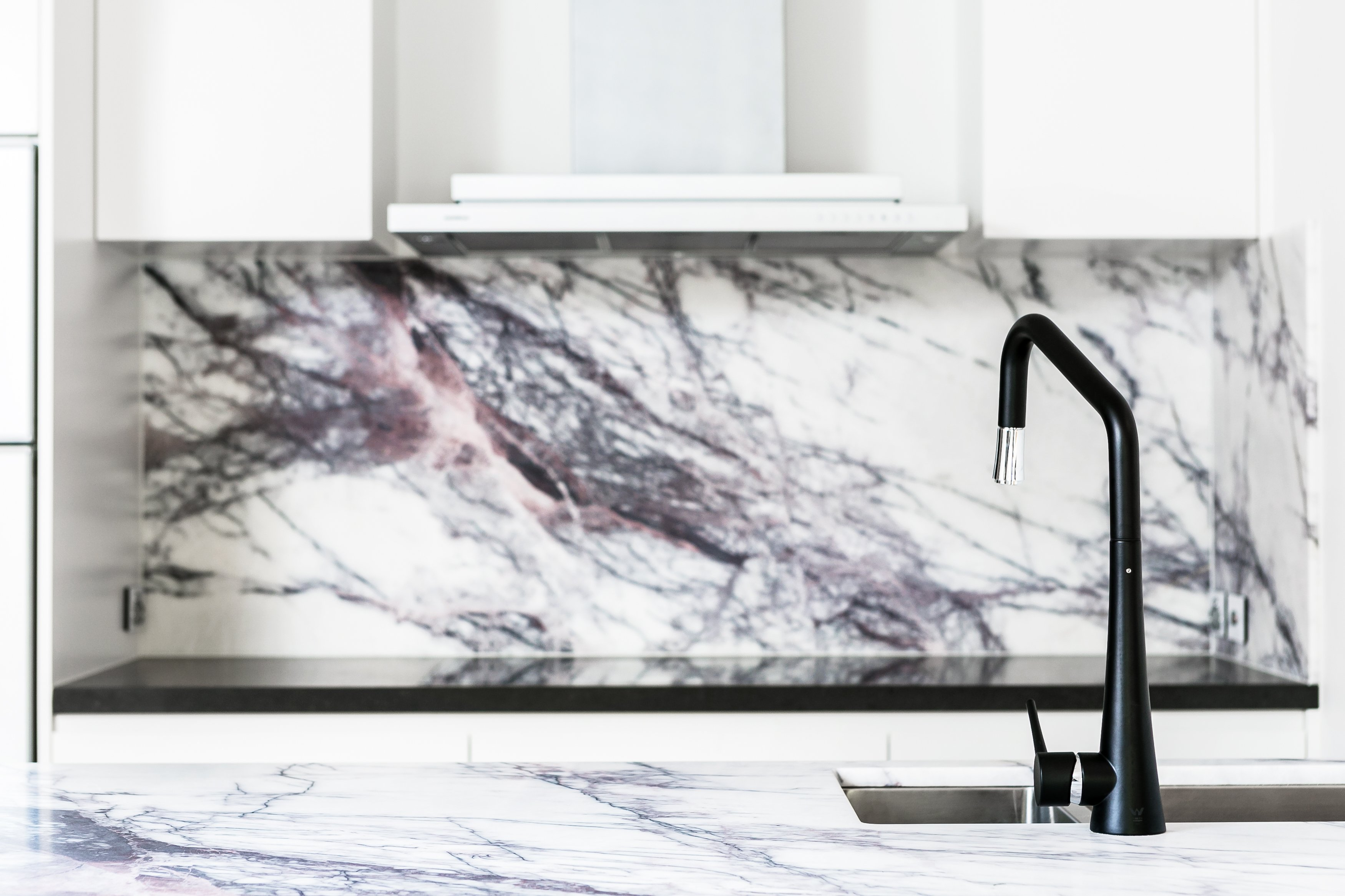 The main countertop and backsplash share a bold, white and black granite slab that highlights the minimalist white nature of the kitchen, contrasting with the clean lines.