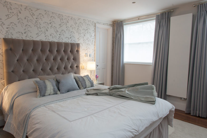 The primary bedroom adds a dash of texture to the muted greys and browns of the home, with floral wallpaper and a large button tufted headboard.