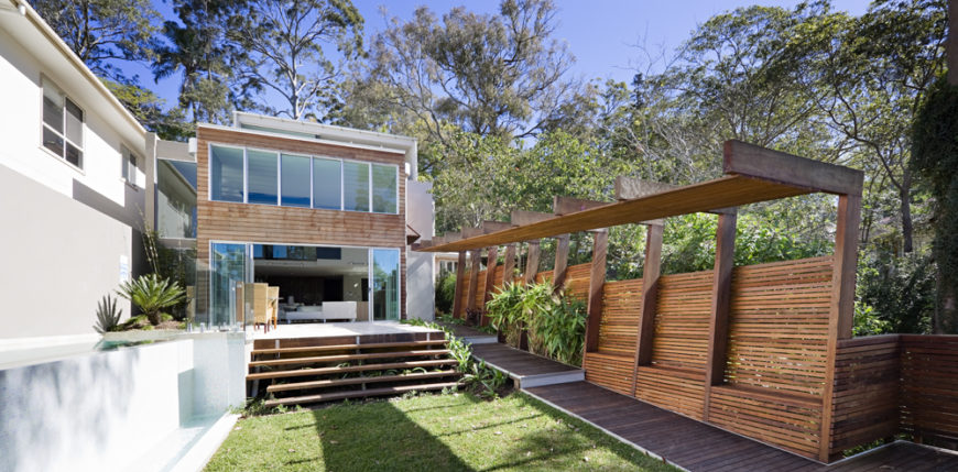 The back yard is framed by a raised lido pool at left and angled wood panel fence and overhang at right. Retractible glass panels allow the interior to open completely to the outdoors.