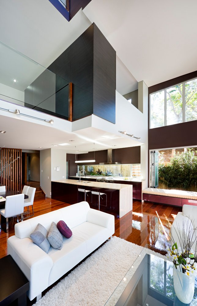 With a vertical, angled look, we can see the upper level spaces overlooking the living room, with a large central dark wood wall dividing the area. The bold mixture of colors and texture throughout is highlighted by the two full stories of windows wrapped around.
