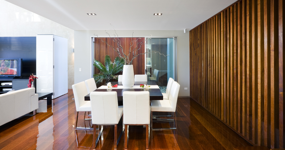 Dining space accented with wooden panel wall along with glossy hardwood flooring. It has a dark wood dining table with white chairs and a lovely centerpiece.