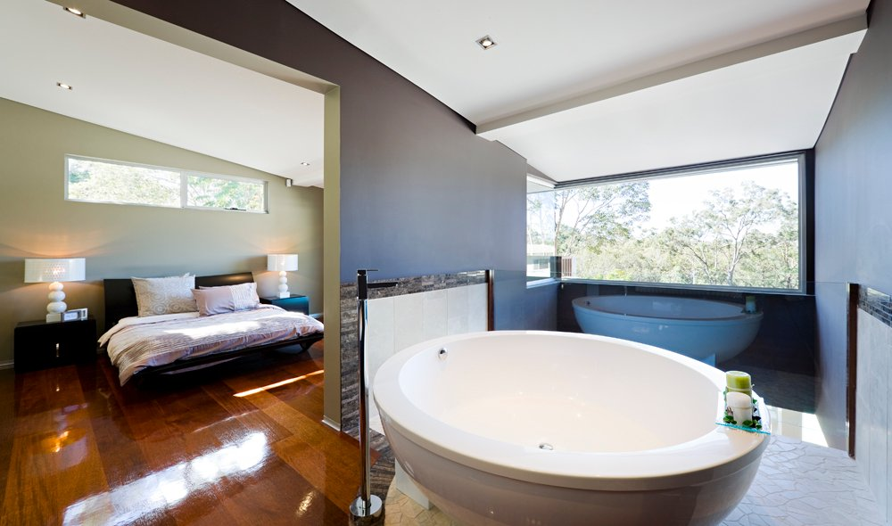Contemporary primary bedroom with an open wall that leads to the bathroom. It has a black bed paired by matching nightstands with white table lamps.