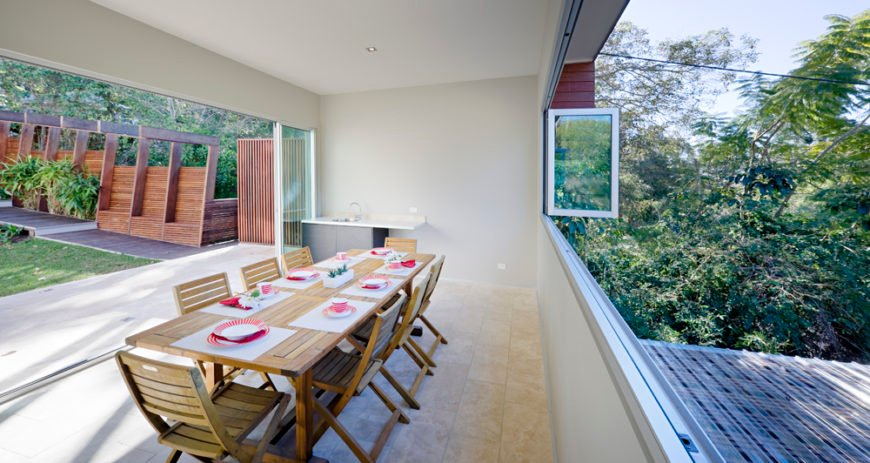 The pool house can be fully opened to the elements, with a full width set of retractible windows mirroring the doors. Spartan accommodations allow for a versatile space, with a single large wood dining table set at center.