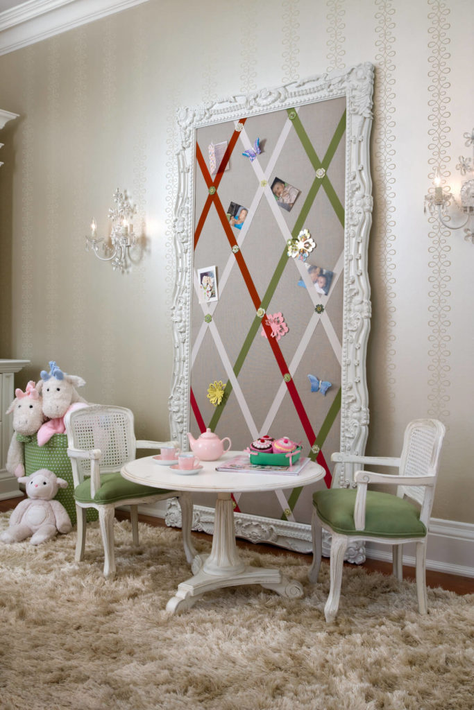 A fabric-covered board with criss-crossing ribbons in an ornate mirror frame makes a lovely memo board. It sits behind a distressed miniature dining set perfect for tea parties with the bin of stuffed animals to the left.