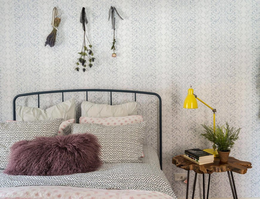 Adorning the detailed wall is a trio of dried flowers, used as an inexpensive art piece over the simple thin metal frame bed.