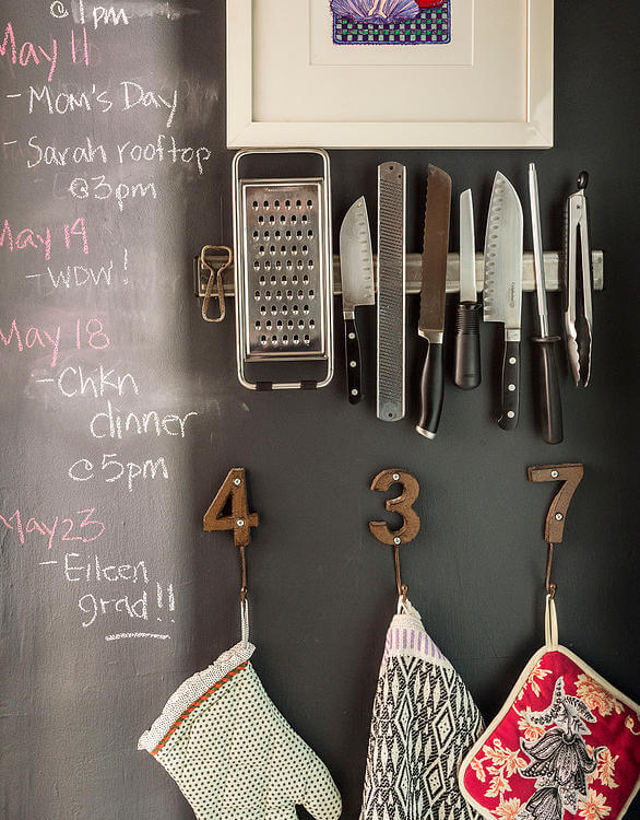 "Magnetic knife rack and ""number"" hangers cling to the chalkboard wall, here adorned with calendar notes."
