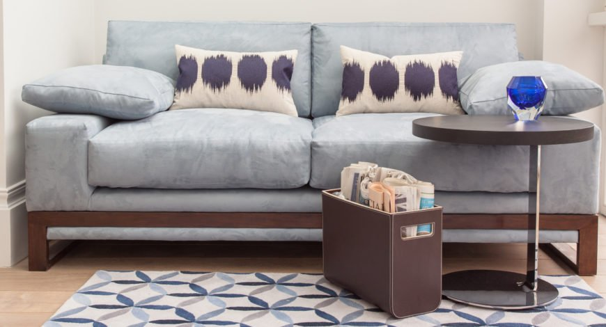 This unique sofa design features sky blue upholstery over a contemporary wood frame, with extra thick cushioning. A circular modern wood and metal table stands on blue and white patterned area rug before it.