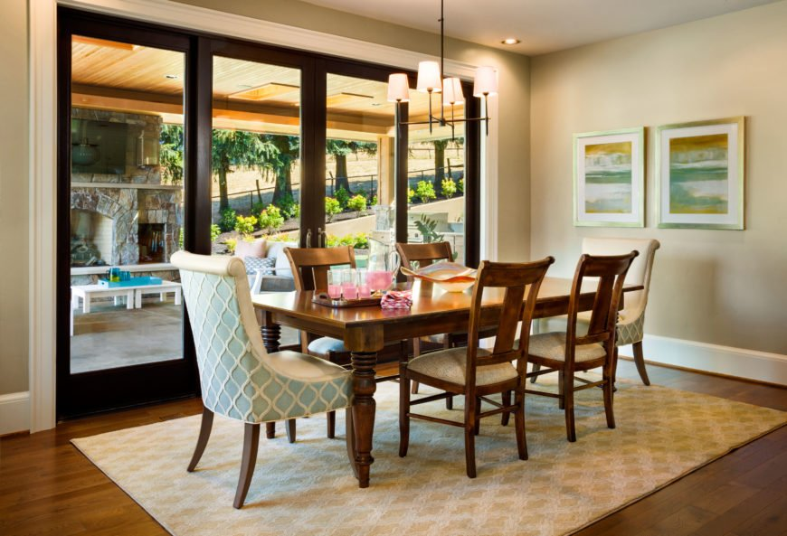 The dining room is just off of the kitchen and connected to both the kitchen and living room. The soft blue and white upholstery of the two chairs at the head of the table pull color from the two paintings on the right wall. Just like in the living room, glass doors lead out into the backyard, this time to the covered patio.