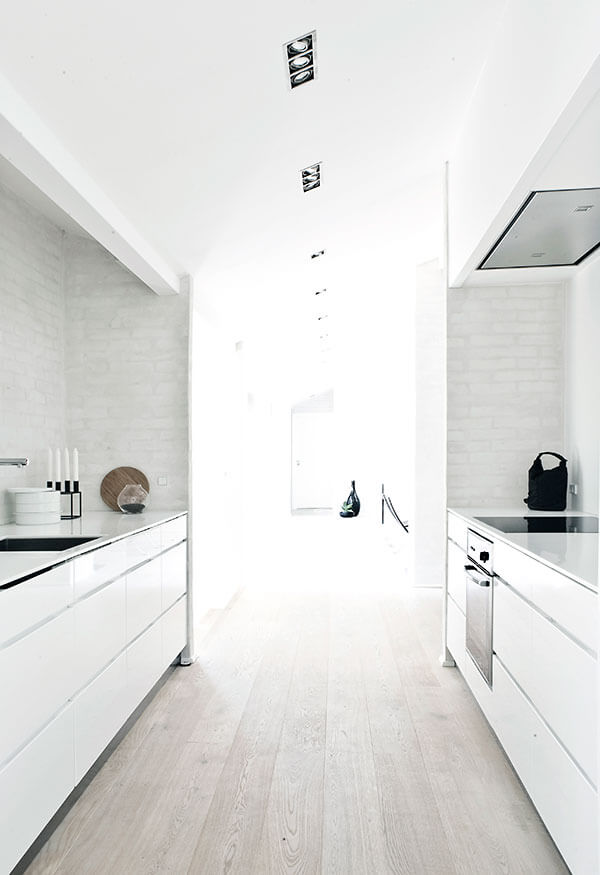 A series of subtle recessed light sources tracks the length of the upper level, filled with complementary natural light. The kitchen flows openly in this lengthy space, with sleek white countertops flanking.
