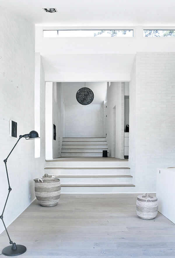 This lengthy hallway shows two sets of stairs dividing the plateau segments, with light natural hardwood flooring pairing with white brick walls for an austere, neutral palette. Narrow horizontal slit windows above allow natural light throughout.