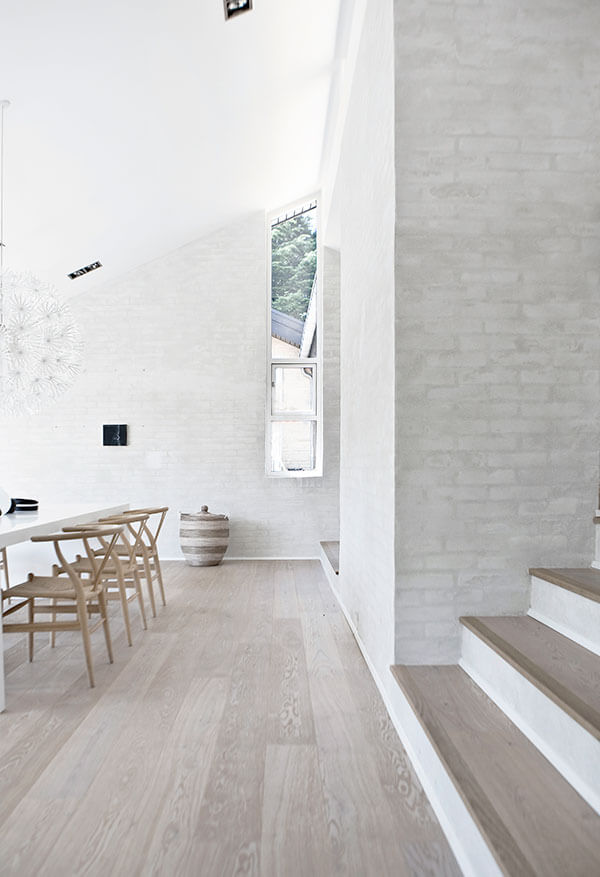 With this image, we see another set of vertically aligned windows reaching toward the sloped ceiling right as it peaks. The soft white tones of the brickwork surrounding help to illuminate the space.