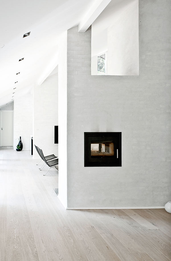 The dividing walls flanking the living room space each hold two-sided gas fireplaces, adding function and contrast to the area. Black leather, metal frame seating complements the look.
