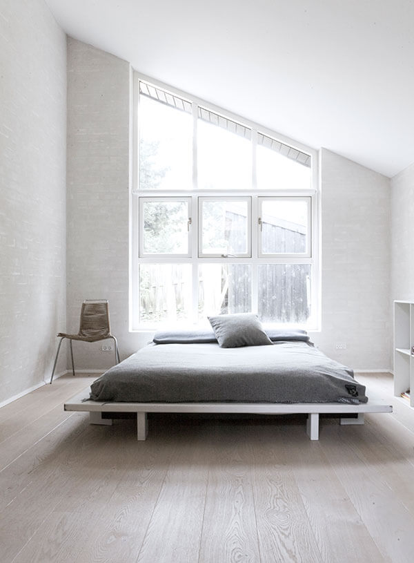 Primary bedroom evokes the vertical windows of the main body of the home, widened to accommodate the entire space. A platform bed holds the center, flanked by an accent chair and white cubic shelving.