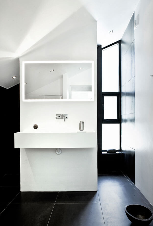 Primary bath, contrasting with the body of the home, appears in black floor and wall tiles, punctuated by an all-white vanity at center.