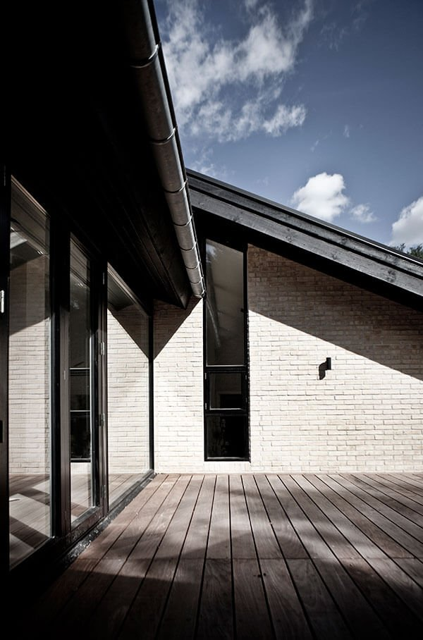 The upper level features this dark natural wood patio below the brick and glass walls, respectively.