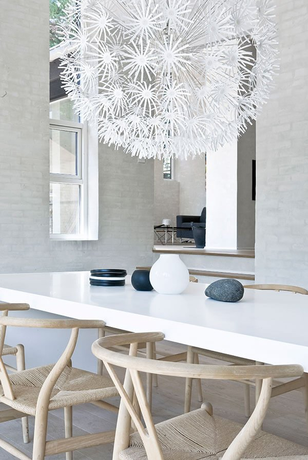 With an angled view, we can see the upper living room plateau across the dining room table. Soft textured natural wood chairs in foreground neatly find a warm tone, complementary to the flooring.