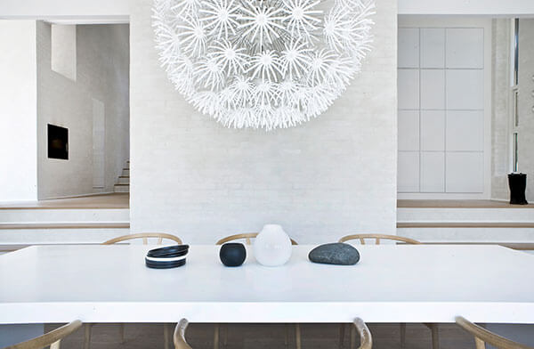 Over the dining room table we see this striking white dandelion sculpture, evoking a playful sense within the neutral aesthetic of the home.
