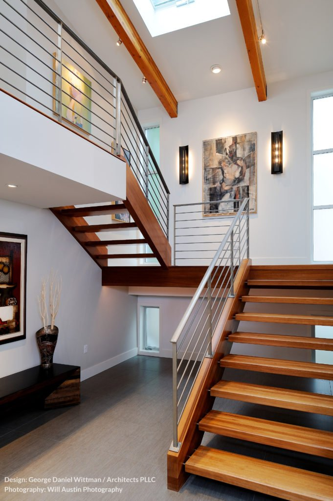 The secondary staircase is an all-wood construction, with metal railings. This stands directly under a large skylight flanked by more exposed natural wood beams.