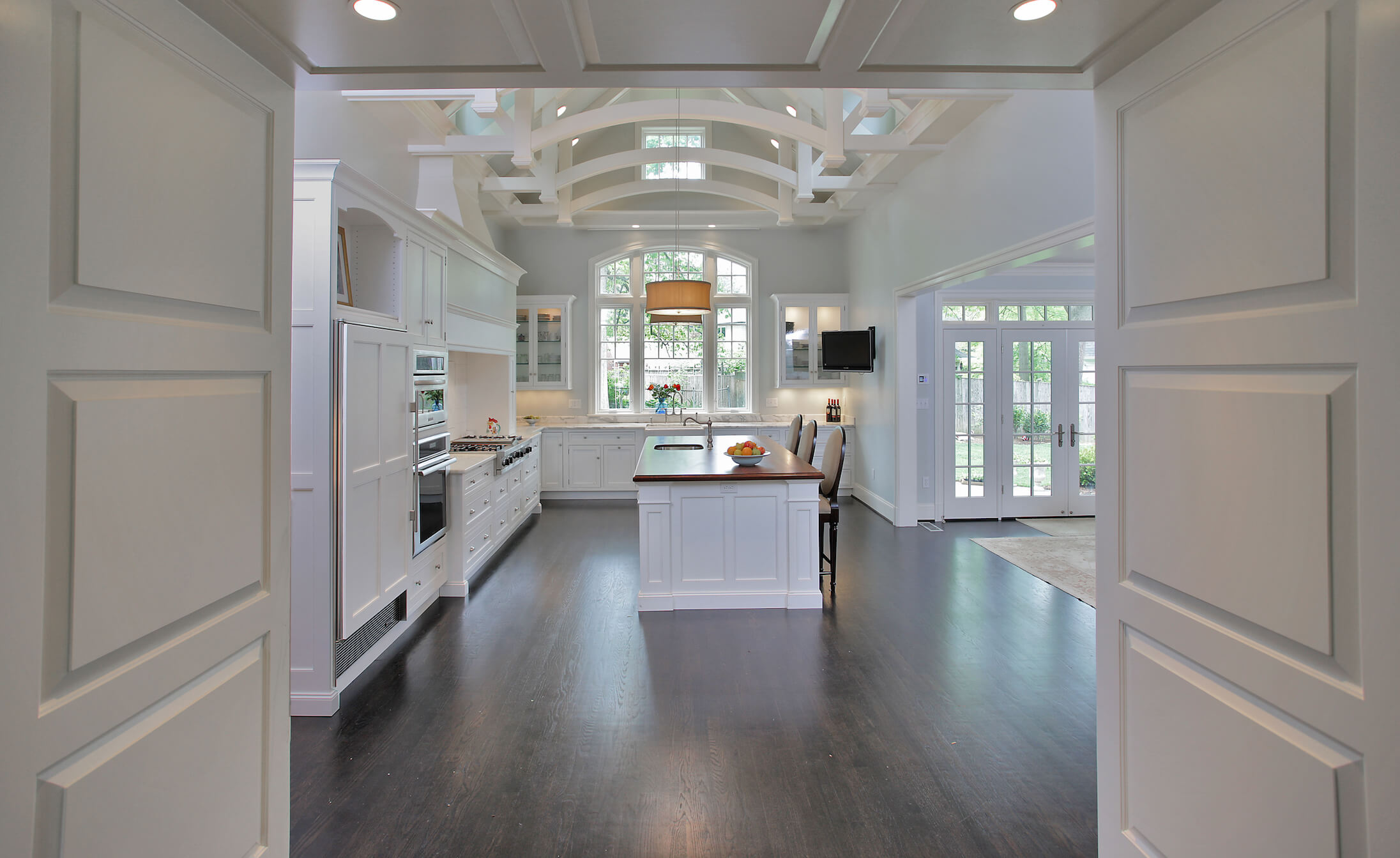 Viewing the kitchen through an entry hall, we see a wide swath of dark hardwood flooring, contrasting with the white cabinetry and walls.