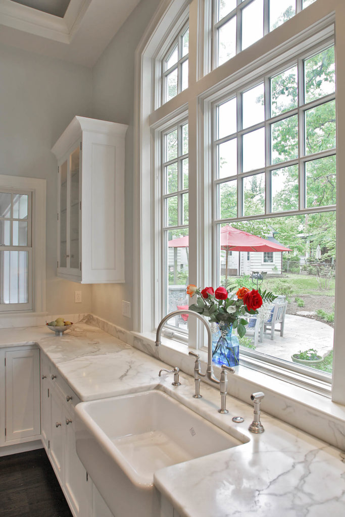 Countertops were replaced with white marble throughout, adding an elegant touch below the large centerpiece kitchen window.