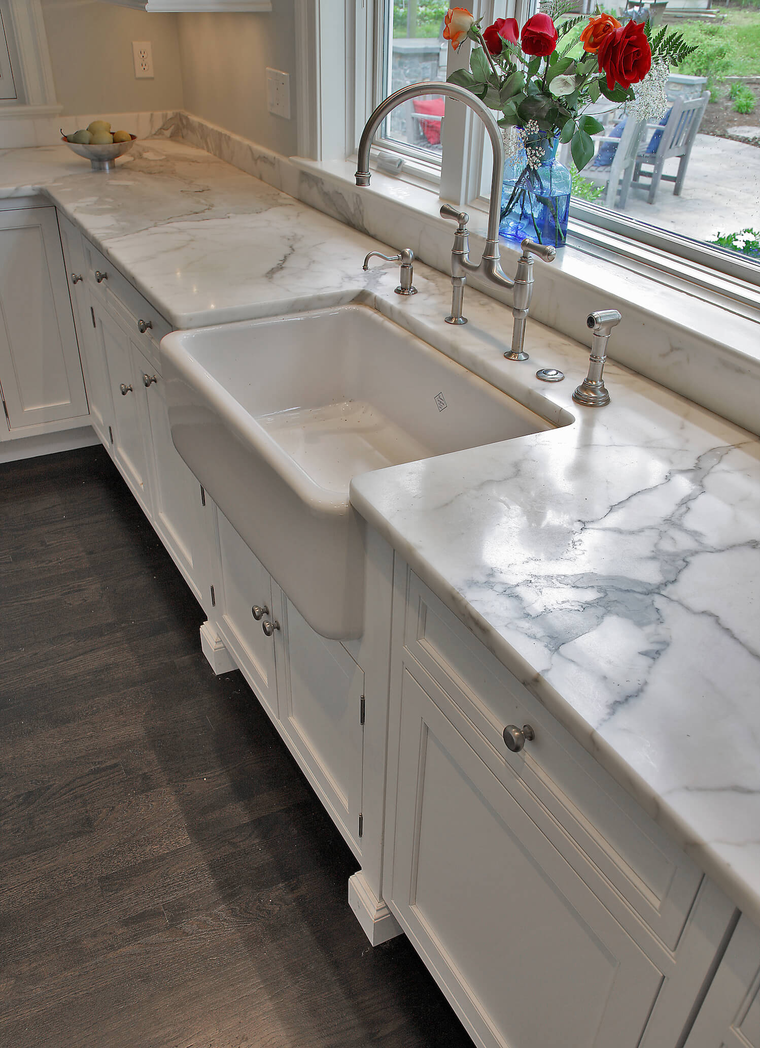 Angling slightly down, we take in the new farmhouse sink and white cabinetry with fresh hardware. The oak flooring was stained dark as per the owners' preference.