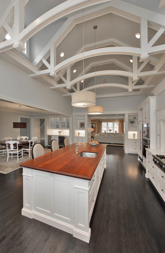With a view from the opposite end of the kitchen, we have a better look at the recessed lighting and dormer windows in the ceiling space. The dining area can be seen at left, with dark wood table and white chairs centered over a floral area rug.
