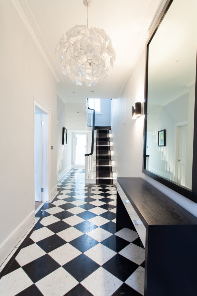 The central hallway features a black and white checkered tile floor, adding a playful sensibility and matching with the minimalist side table and staircase seen here. Another spherical chandelier, with floral shapes, appears in this space.