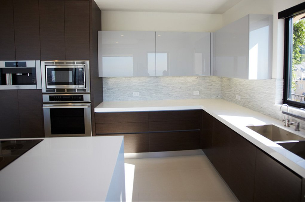 The stark white countertops provide high contrast to the dark stained, minimalist wood cabinetry. In this corner, we see glossy white upper cupboards as well, with thin tile backsplash sandwiched between.
