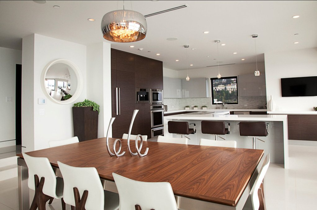Returning to a wide view of the dining and kitchen space, we see a large natural wood topped dining table, floating slightly above the structure, below a chromed barrel chandelier. Pendant lights over the island combine with recessed lighting in the kitchen.