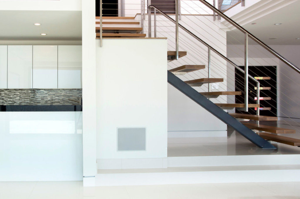 This central staircase is a standout feature in the home, with a metal beam spine supporting individual wood plank steps between wire and stainless steel railings. The flooring and walls here are stark white as well.
