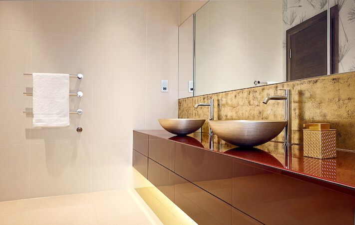 Another bathroom evokes an ultra-modern style akin to that of the kitchen, with sleek red cabinetry below a pair of stainless steel vessel sinks. Under-cabinet lighting highlights the soft white tone of the floor and wall tiles.