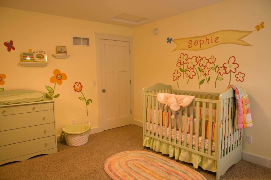 The nursery is filled with floral decals over soft green dresser and crib.