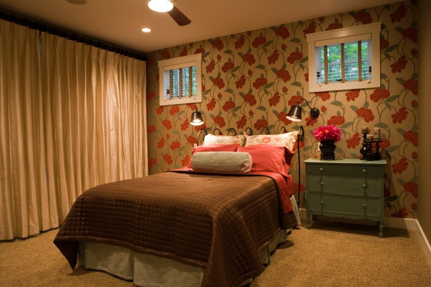 Primary bedroom is filled with rich hues, including the bold floral wallpaper at far end. Brown and red bedsheets match the theme, over beige carpeting.