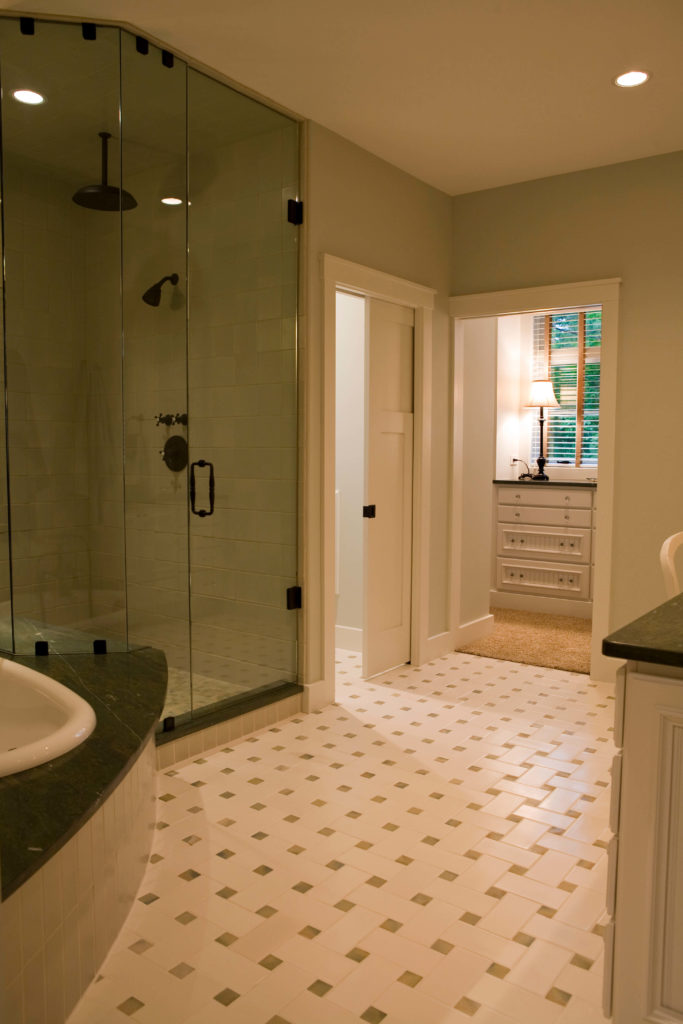 Here's a second bathroom, sporting overlapping white tile flooring design beneath another class enclosure shower. Water closet resides behind a pocket door.