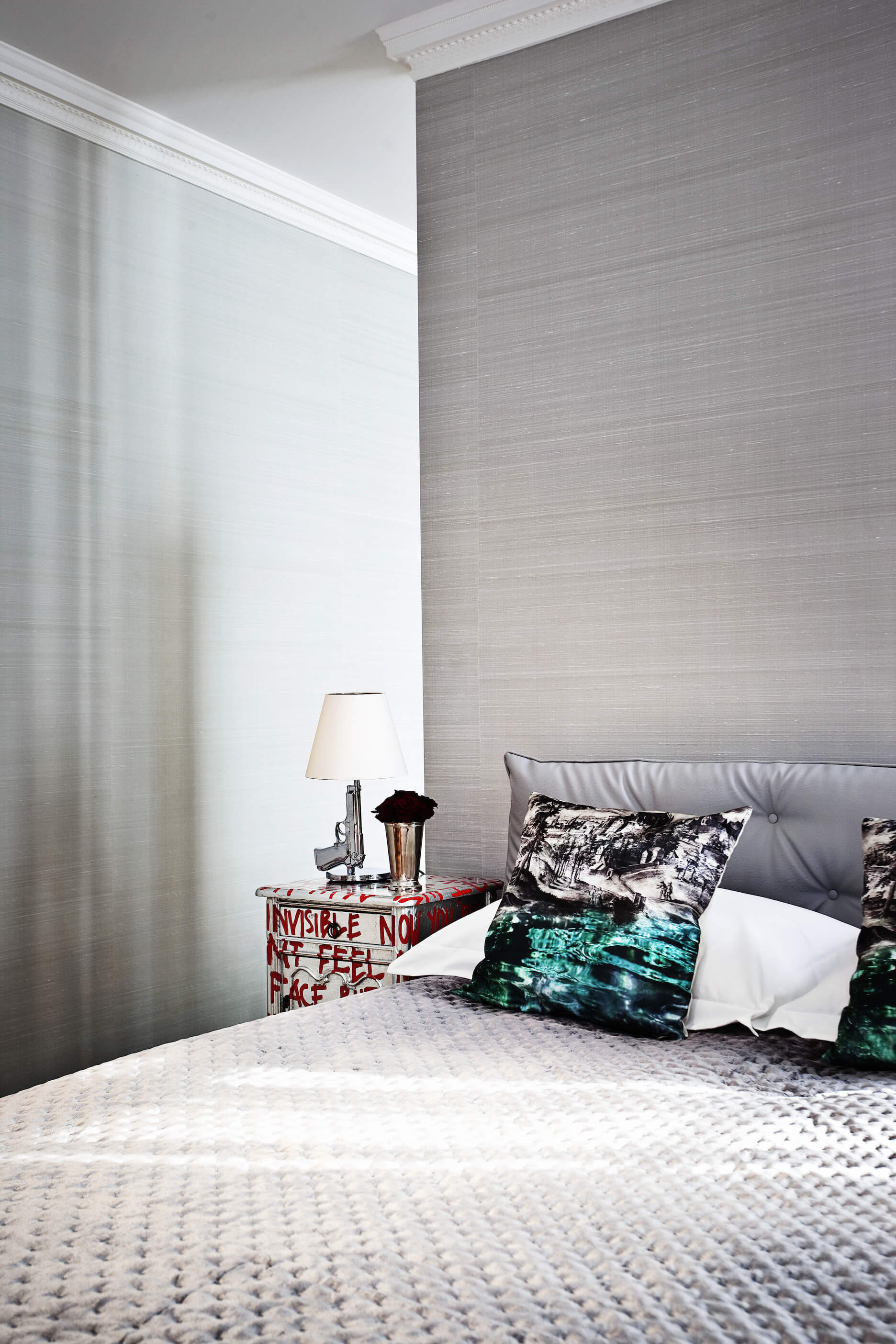 Another bedroom, in a complete turn of style, stands out in silver tones, with brushed look walls above a uniquely textured bed set.