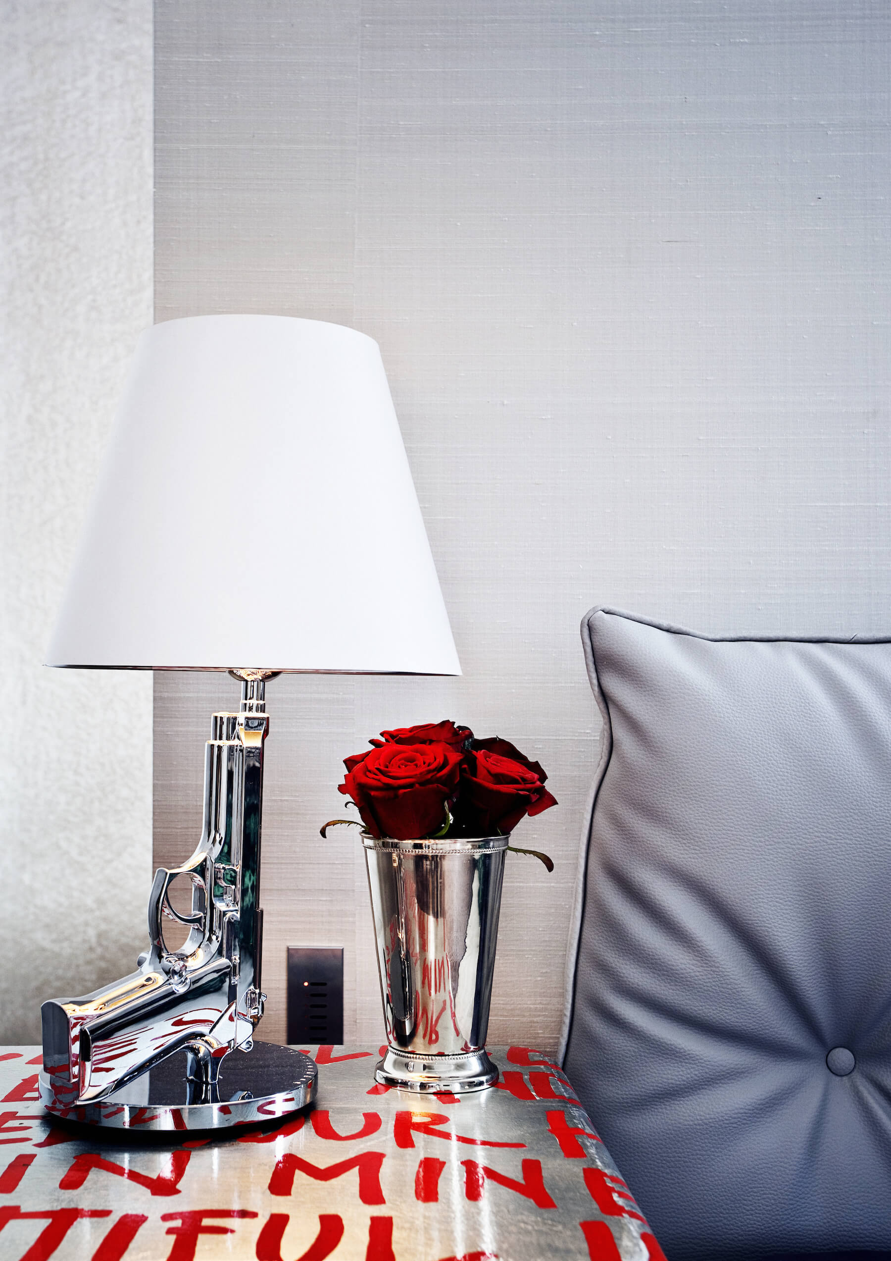 Silver toned bedside dresser with red text painting holds a chromed vase and this striking handgun-design lamp.