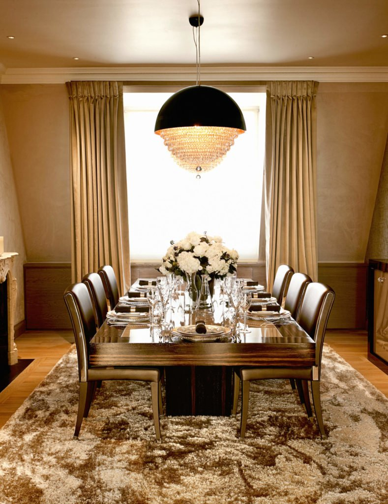 Dining room holds this extra thick wood dining table, paired with a set of leather upholstered side chairs beneath a unique chandelier combining a spherical body and traditional crystal structure. Gold hued drapes accent the rich tone of the room.