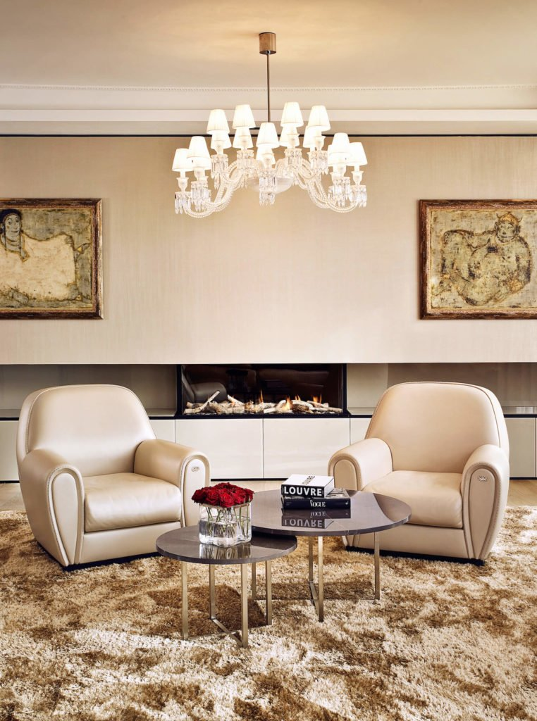The bespoke living room combines traditional opulent details, like the chandelier and pair of cream leather club chairs, with a horizontal array of sleek minimalist cabinetry and open design fireplace. A pair of marble topped coffee tables stand over the thick brown rug on the hardwood flooring.