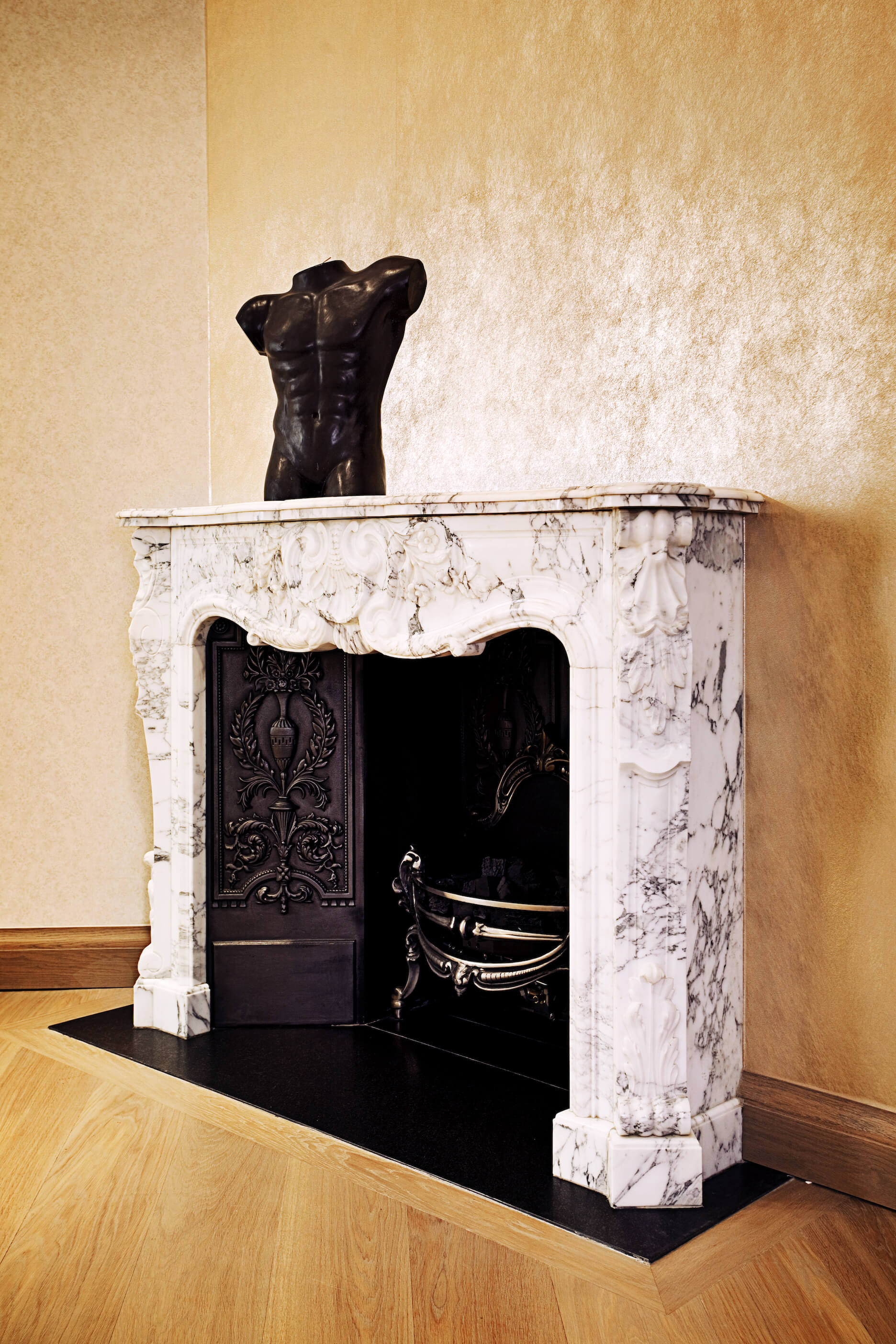 Standing within the dining room, this marble wrapped fireplace stands out with its bright, contrasting tones and rich, carved details.