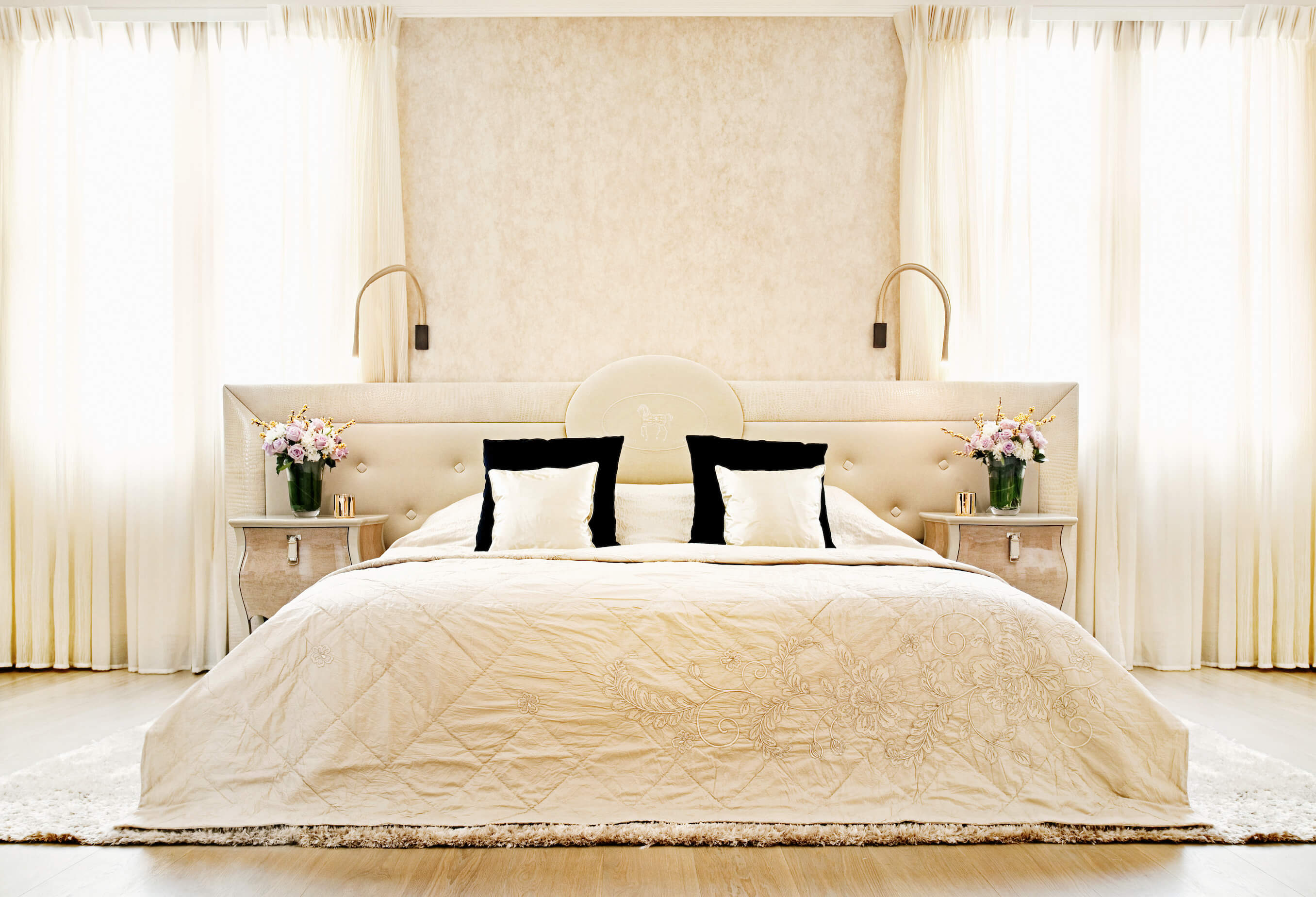 Primary bedroom suite is awash in bold cream tones, from the drapes to the large, button tufted headboard, flanked by a pair of carved wood dressers. Another thick area rug holds the furniture in this room over hardwood flooring.