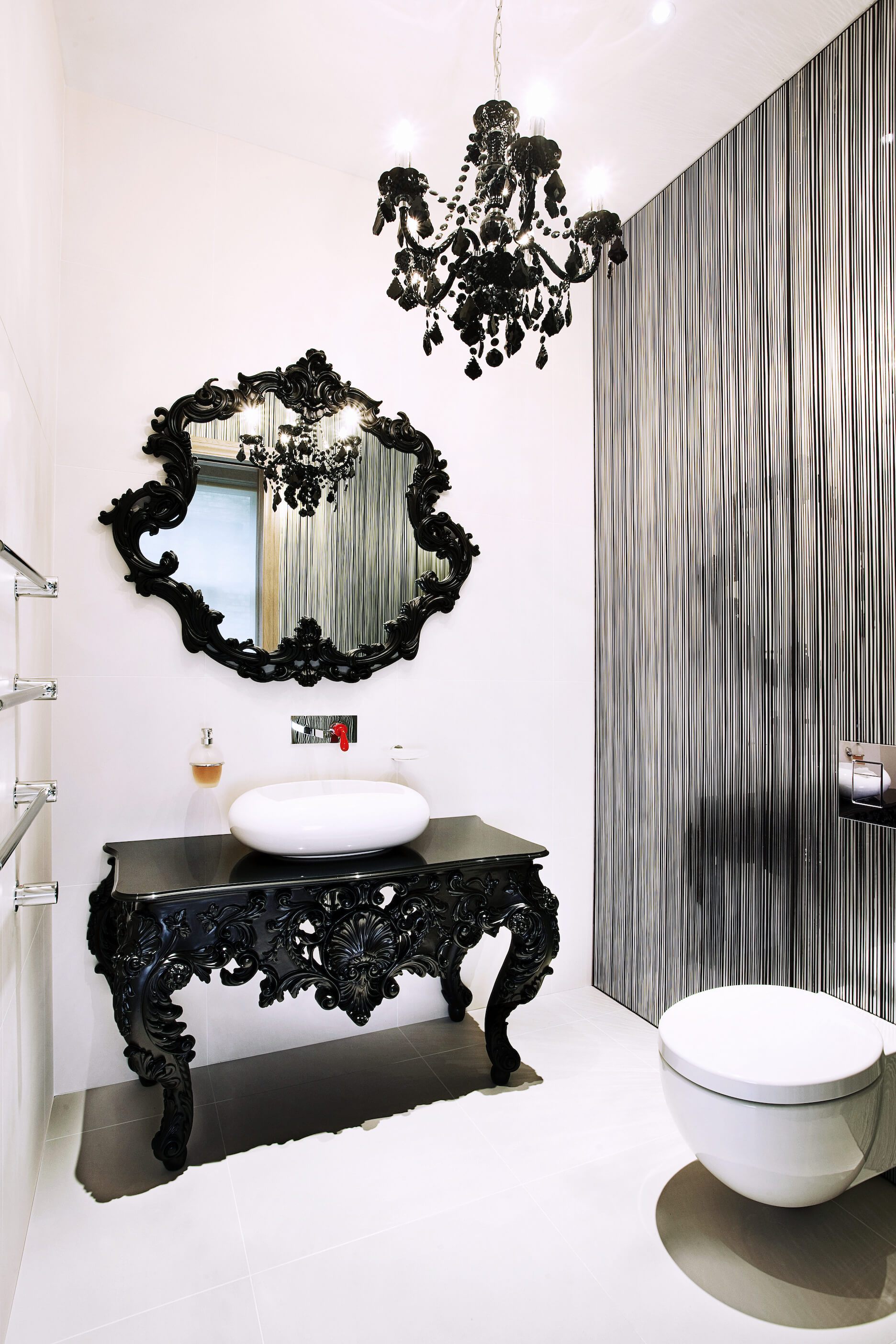 Finally, we have another completely distinct bathroom. This example sports an ornate, traditionally styled table vanity in black with white vessel sink, below a complementary black framed mirror. Silver vertical stripe wall contrasts with white tiling throughout.