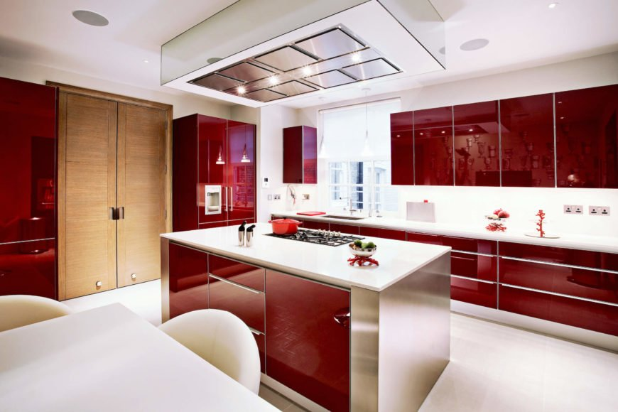 The red modern kitchen leaps out with grand contemporary style, holding red glossy cabinetry and stainless steel island with white flooring and countertops. This look contrasts deeply with the living room, offering a fresh sense of luxury in the space.