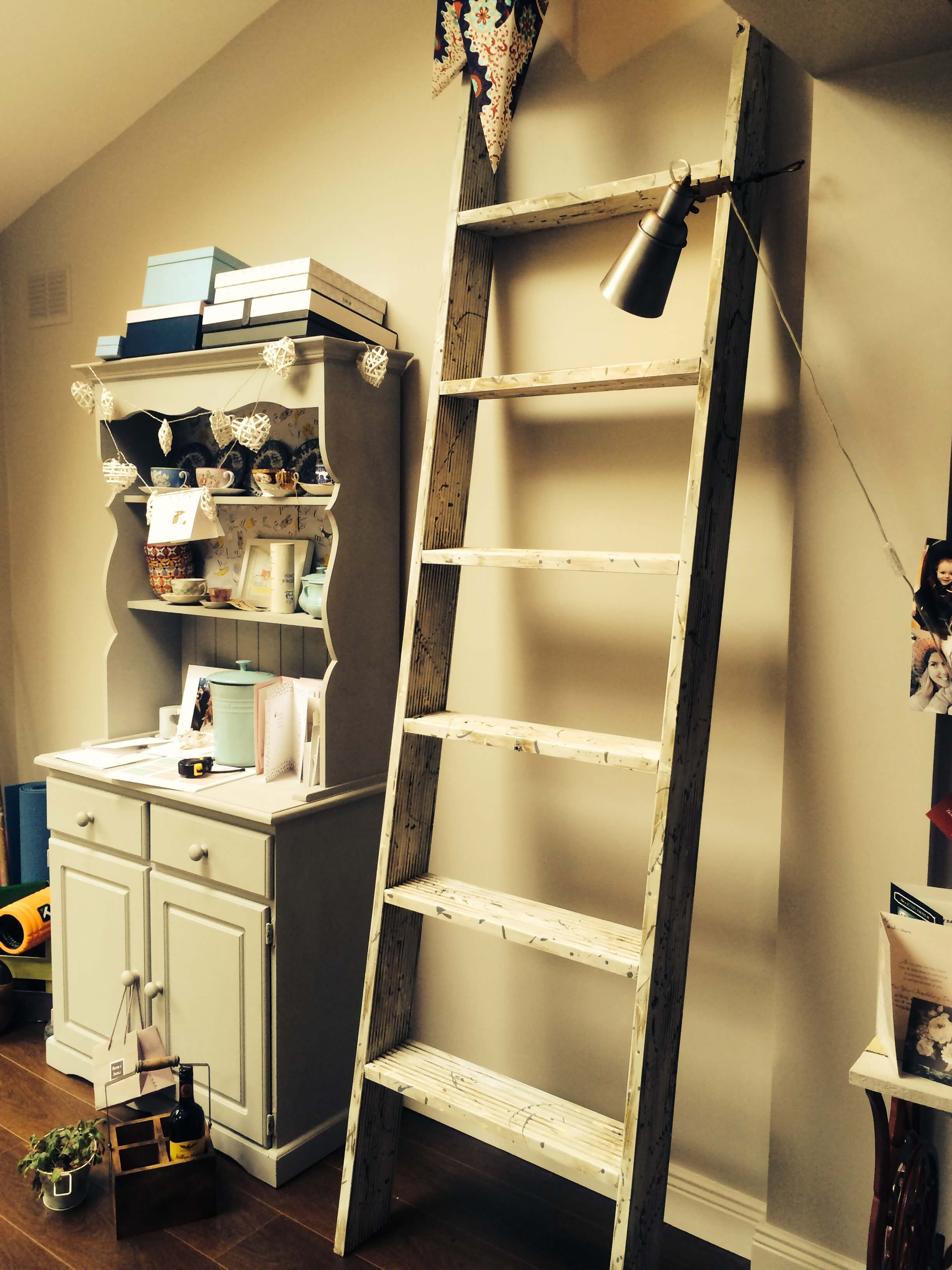 A side view of the shelving without any thing on the shelves. It perfectly fits into a small nook next to the vintage cabinet.