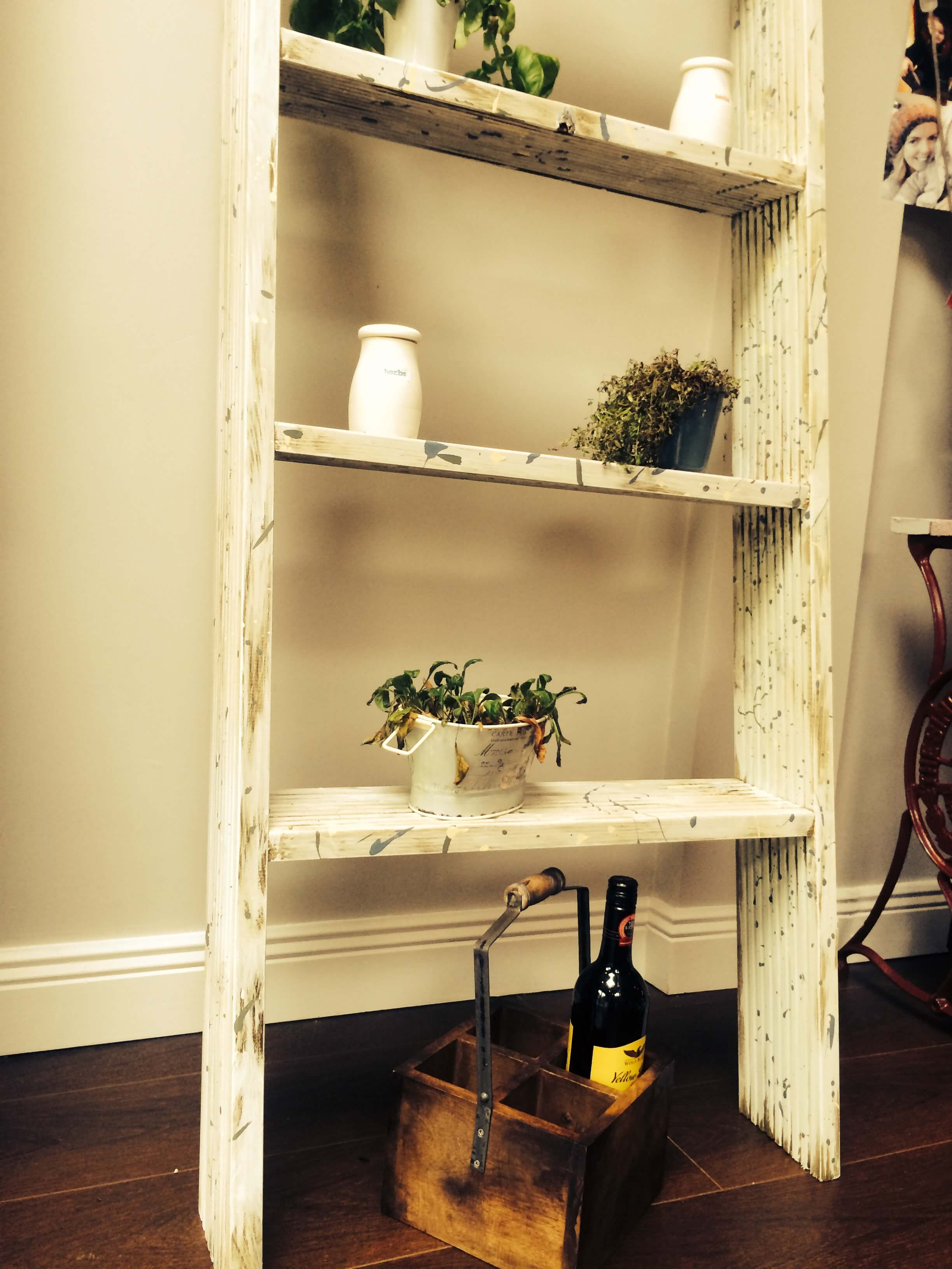 The shelf with added accents, including potted herbs, a wine holder, and dried herb containers.