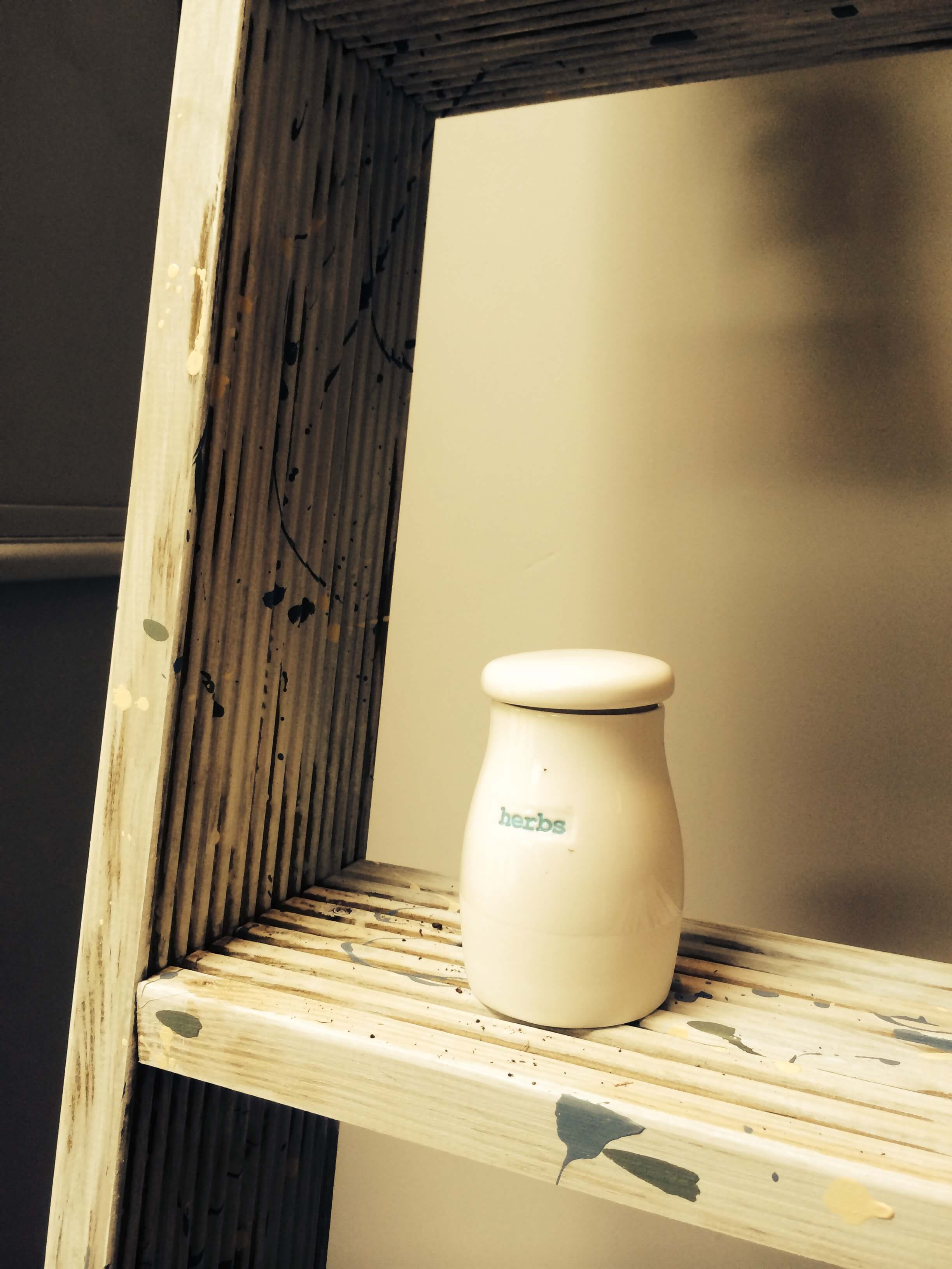 A close up of the shelf and an herb container accent sitting upon it.