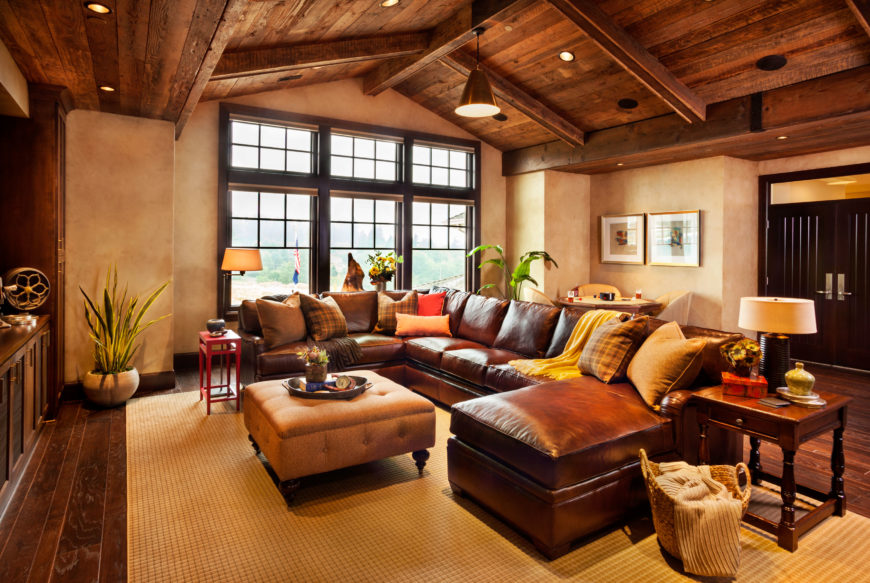 Another of this home's entertaining rooms is on the second floor. This room is more rustic in style, with an exposed wooden ceiling and textured adobe-style walls. The leather sectional has a chaise lounge on one end. This room features fantastic brick and reclaimed wood accents.