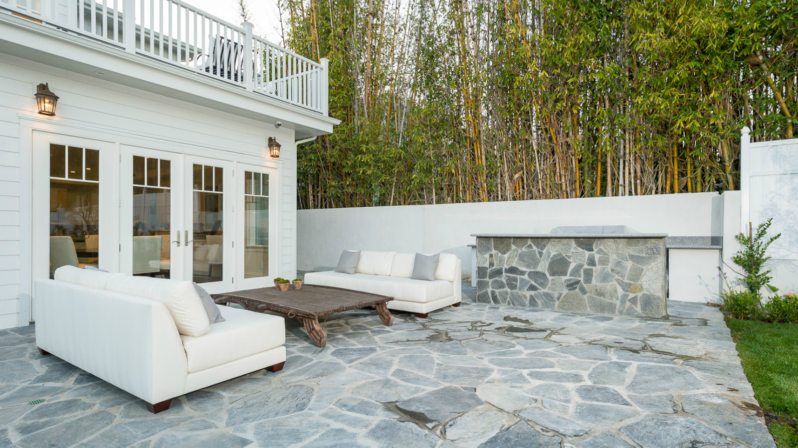 The backyard patio is in gray flagstone with a heavy, solid coffee table between two cozy sofas just below the balcony outside of the primary bedroom.
