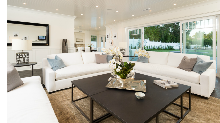 The living room is divided into two separate, distinct spaces that flow together with a similar color palette and design strategy. Half of the living room opens into the fenced in backyard via a sliding glass door. The open archway on the left leads into the kitchen and breakfast nook.